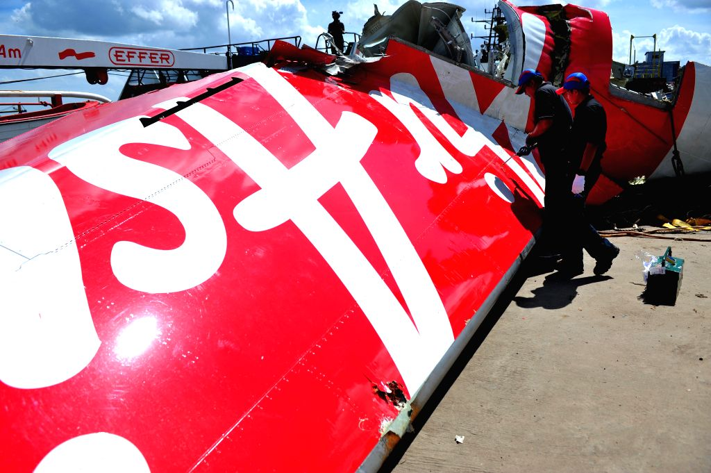 Members of Indonesia's National Transportation Safety Committee work on the tail of AirAsia Flight QZ8501 at Kumai port, Pangkalan Bun, Central Borneo, ...