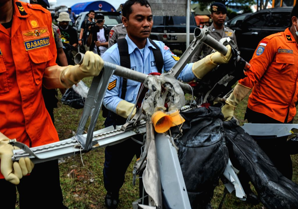 TNI and Search and Rescue (SAR) crew members carry debris of AirAsia flight QZ8501 from USS Navy helicopter at Iskandar Air Base, Pangkalan Bun, Central ...