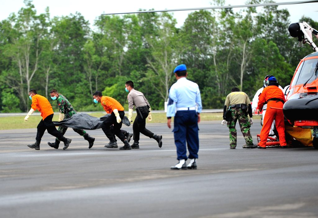 Members of the National Search And Rescue Agency unload the body of a victim of AirAsia Flight QZ8501 from a helicopter at Iskandar Air Force Base, in ...