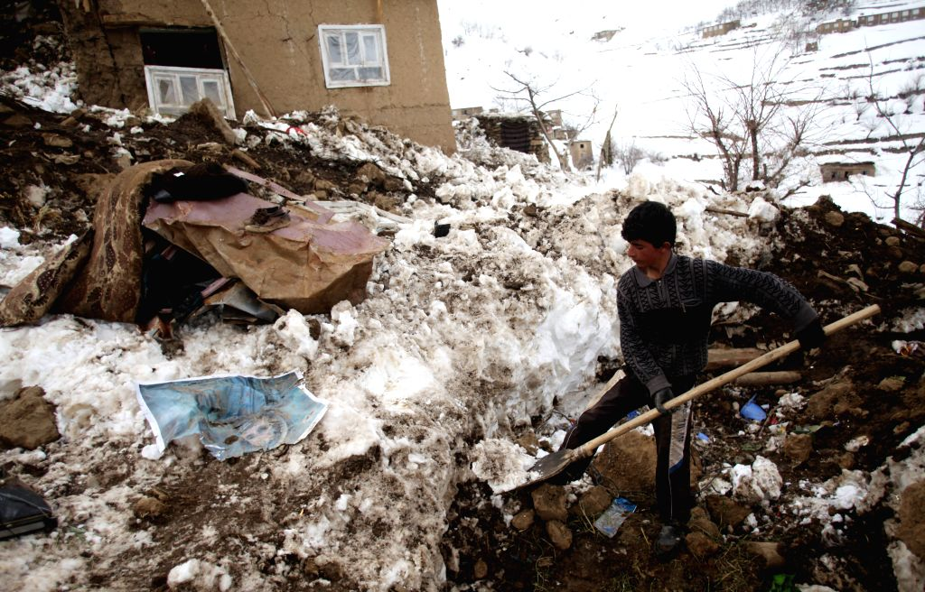 An Afghan child removes snow inside his destroyed house after avalanches in Abdullah Khil of Panjshir province, Afghanistan, March 1, 2015. Afghan government and ...