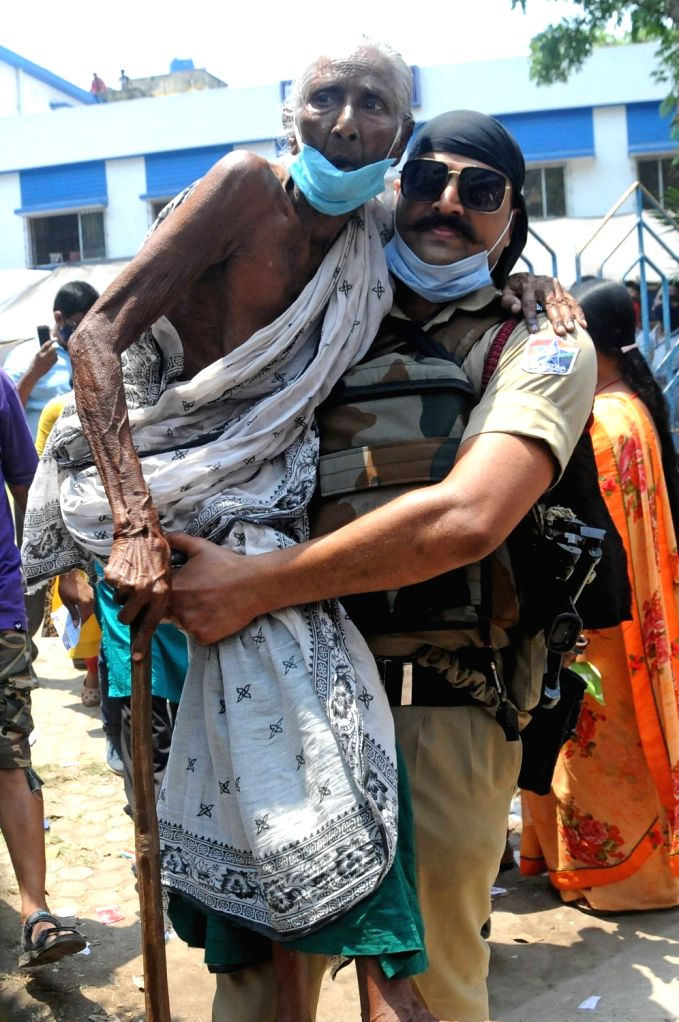 Paramilitary forces personal caring an old woman and comes out from polling station after casting her vote during the 5th phase of State Assembly election at Bidhannagar in Kolkata on ...