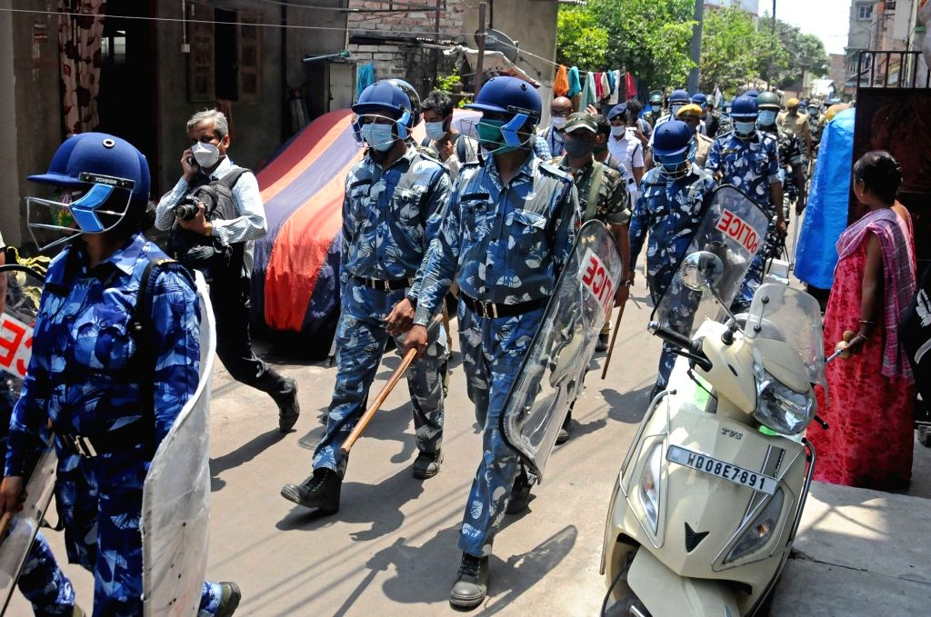 Paramilitary forces personnel along with the State police conduct a route march near a polling station during the 5th phase of State Assembly election at Bidhannagar in Kolkata on Saturday, ...