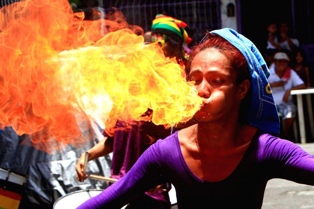 A street performer breathes fire during the feast day of Saint Rita de Cascia in Paranaque City, the Philippines, May 18, 2014. The Saint Rita de Cascia ...