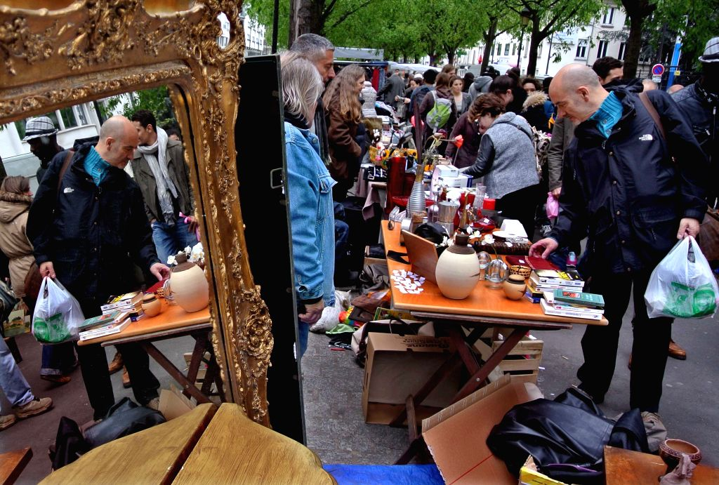Customers choose commodities at a flea market in Paris, France, April 20, 2014. Lots of local residents like going to flea market over the weekend to get useful ...