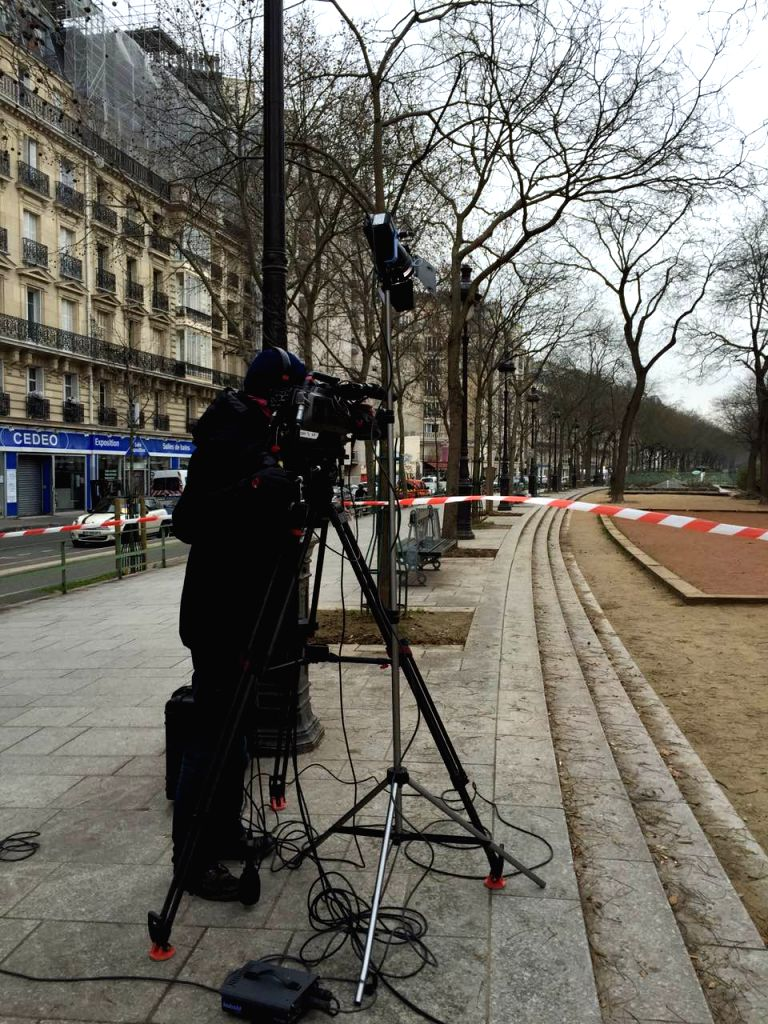 A cameraman works near the Paris office of Charlie Hebdo in Paris, France, Jan. 7, 2015. The office of Paris Prosecutor of the Republic confirmed at least 12 people ...