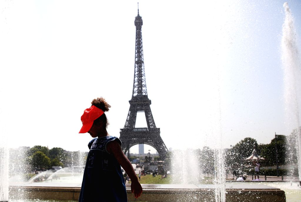 PARIS, July 25, 2019 - A girl poses for a photo with the Eiffel Tower on the backdrop by a fountain at the Trocadero Place in Paris, France, July 25, 2019. Temperature in Paris hit 42 degrees ...