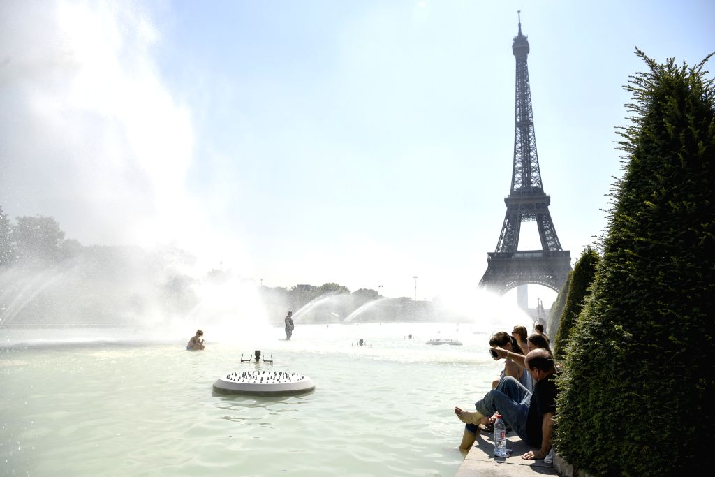 PARIS, July 27, 2018 - People cool themselves beside a pool near the Eiffel Tower in Paris, France, on July 27, 2018.
