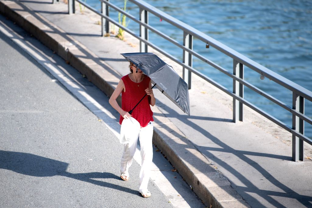 "PARIS, June 28, 2019 (Xinhua) -- A woman walks with a sunshade in Paris, France, June 27, 2019. The national weather center, Meteo France, on Thursday warned of ""exceptional heat peak"" on June 28, placing 4 southern regions on red alert, the highest"