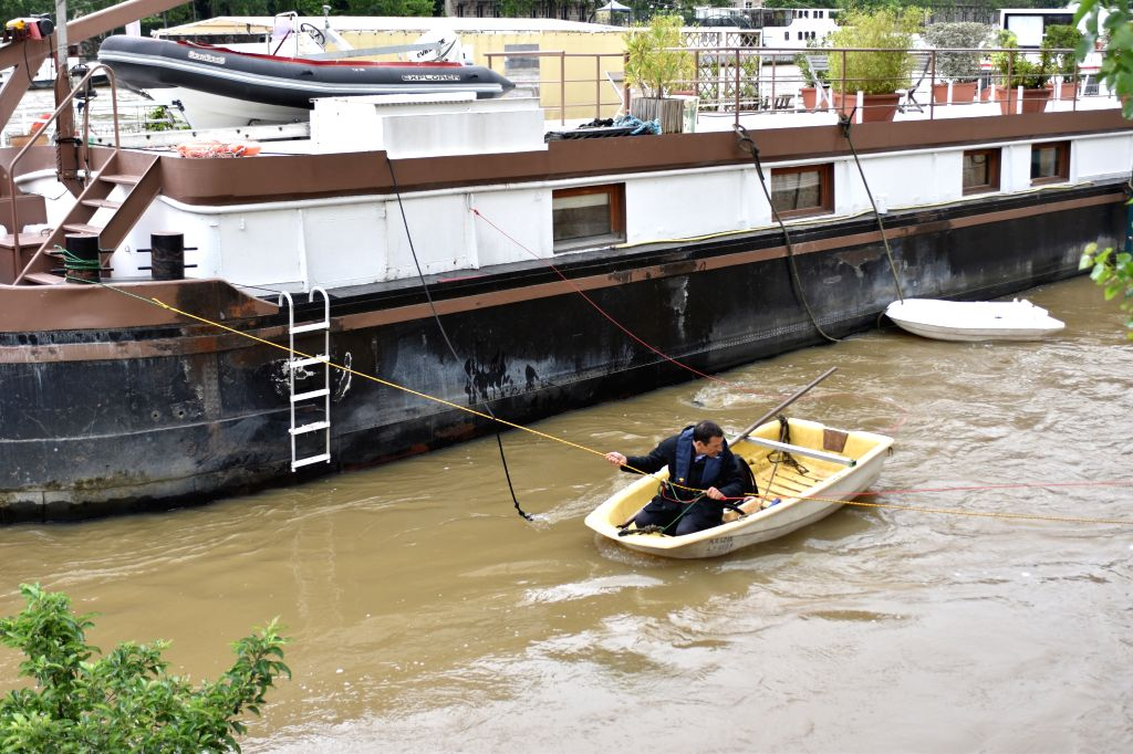 PARIS, June 3, 2016 - A man uses a barge to cross the river in Paris, France, June 3, 2016. Due to heavy rainfall across French cities, flood waters have reached alarming level, forcing thousands of ...