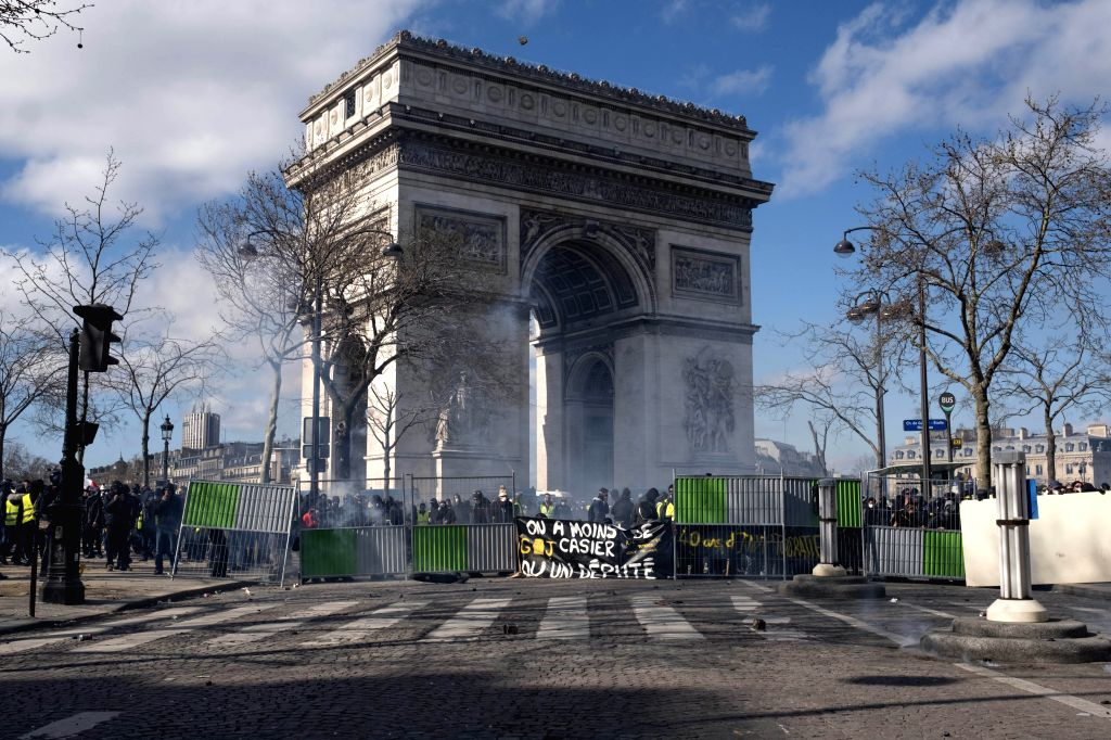 """PARIS, March 16, 2019 (Xinhua) -- """"Yellow Vest"""" protesters clash with riot police at the Arc de Triomphe in Paris, France, on March 16, 2019. French police arrested more than 200 people on Saturday after violence broke out in Paris in a fresh protest"""