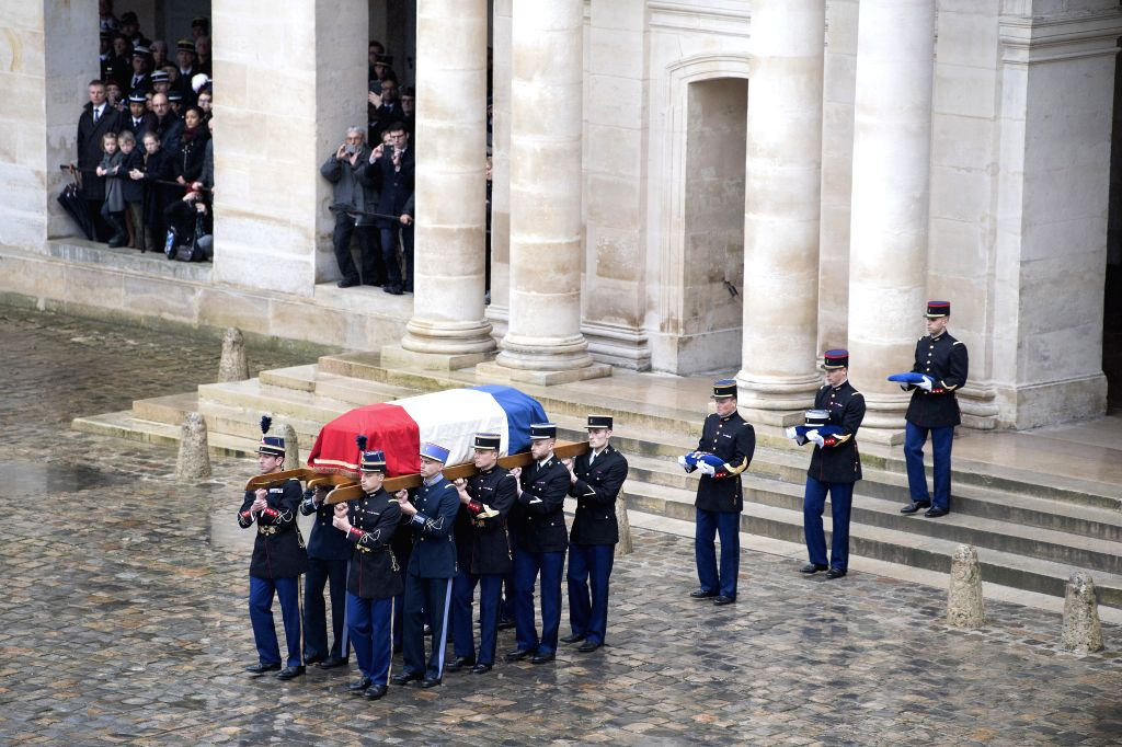 PARIS, March, 28, 2018 French Republican guards carry the flag-draped coffin of the hero officer Arnaud Beltrame in Paris, France on March 28, 2018. Amid rains, a ceremony was held on ...