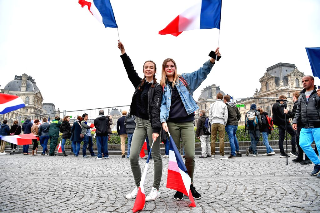 PARIS, May 7, 2017 - People wave French national flags after an estimation showed that Macron won the presidential race in front of the Louvre Museum in Paris, France, on May 7, 2017. Centrist ...
