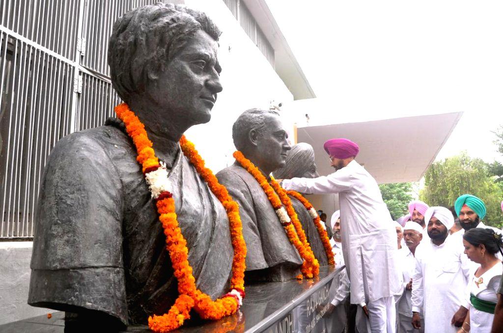 Partap Singh Bajwa, President Punjab Congress offering floral tributes to Indira Gandhi, Rajiv Gandhi at Punjab Congress Bhawan Chandigarh on August 15, 2013. (Photo::: IANS) - Indira Gandhi