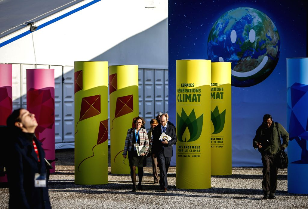 Participants walk at the venue of Paris Climate Change Conference at Le Bourget on the northern suburbs of Paris, France, Dec. 9, 2015. French Foreign Minister and ...