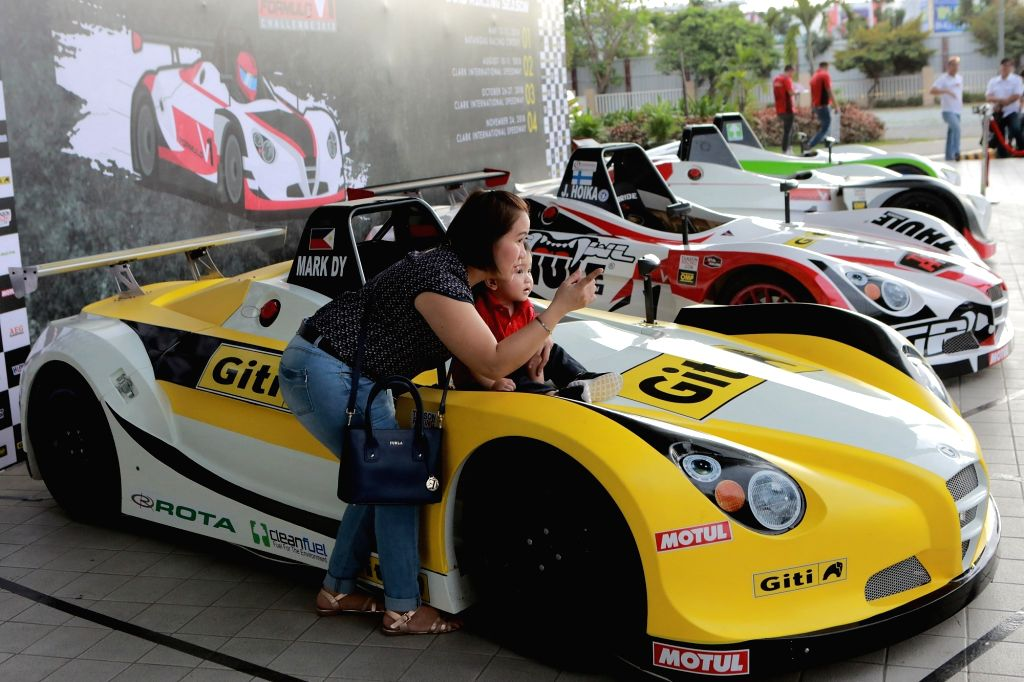 PASAY CITY, April 5, 2018 - A mother and her child pose with a sports car during the annual Manila International Auto Show at the World Trade Center in Pasay City, the Philippines, April 5, 2018.