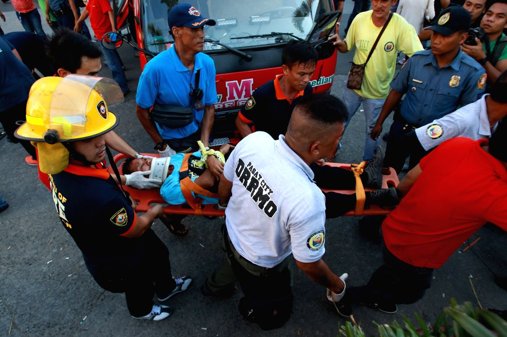 An injured passenger is carried on a stretcher by rescuers away from a derailed train coach in Pasay City, the Philippines, on Aug. 13, 2014. Around 20 ...