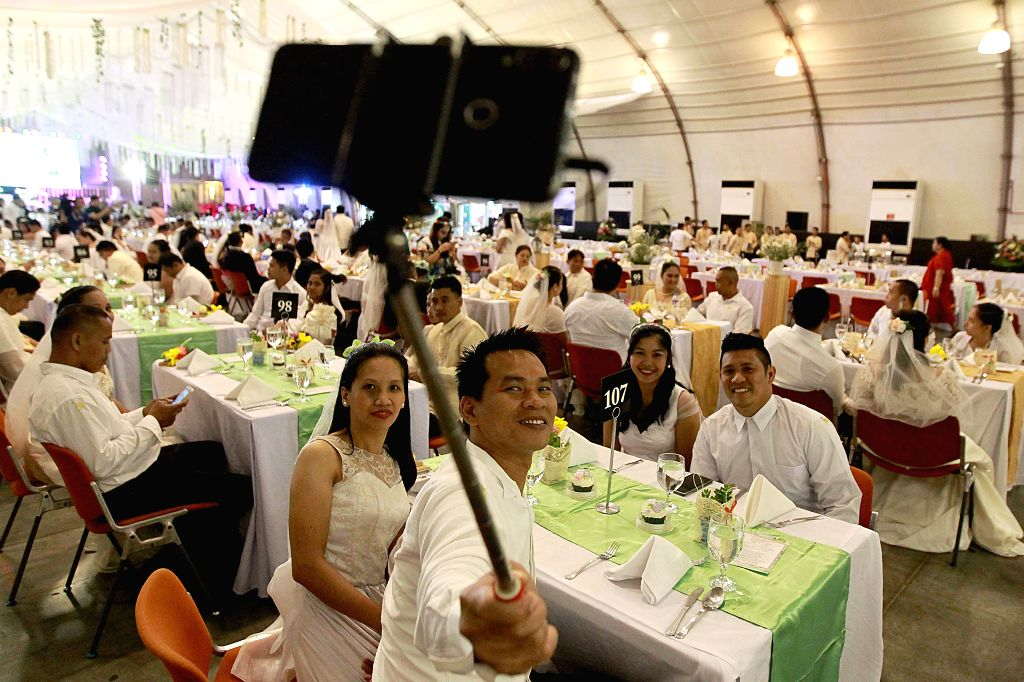 PASAY CITY, Feb. 14, 2019 - Couples take selfies as they wait for the mass wedding ceremony on Valentine's Day in Pasay City, the Philippines, Feb. 14, 2019. More than 300 couples took part in the ...
