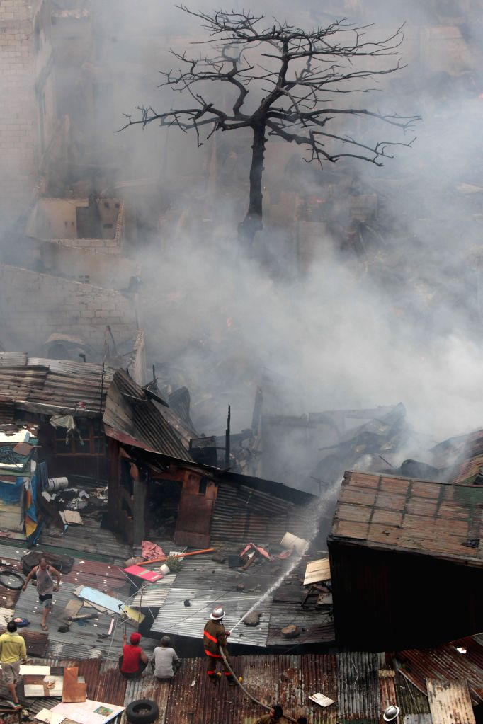 Residents and firefighters try to put out a fire at a slum area in Pasay City, the Philippines, Feb. 19, 2015. 400 shanties were razed in the fire, rendering ...