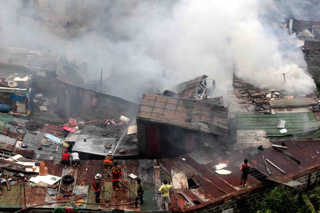 Residents and firefighters try to put out a fire at a slum area in Pasay City, the Philippines, Feb. 19, 2015. About 400 shanties were razed in the fire, left ...