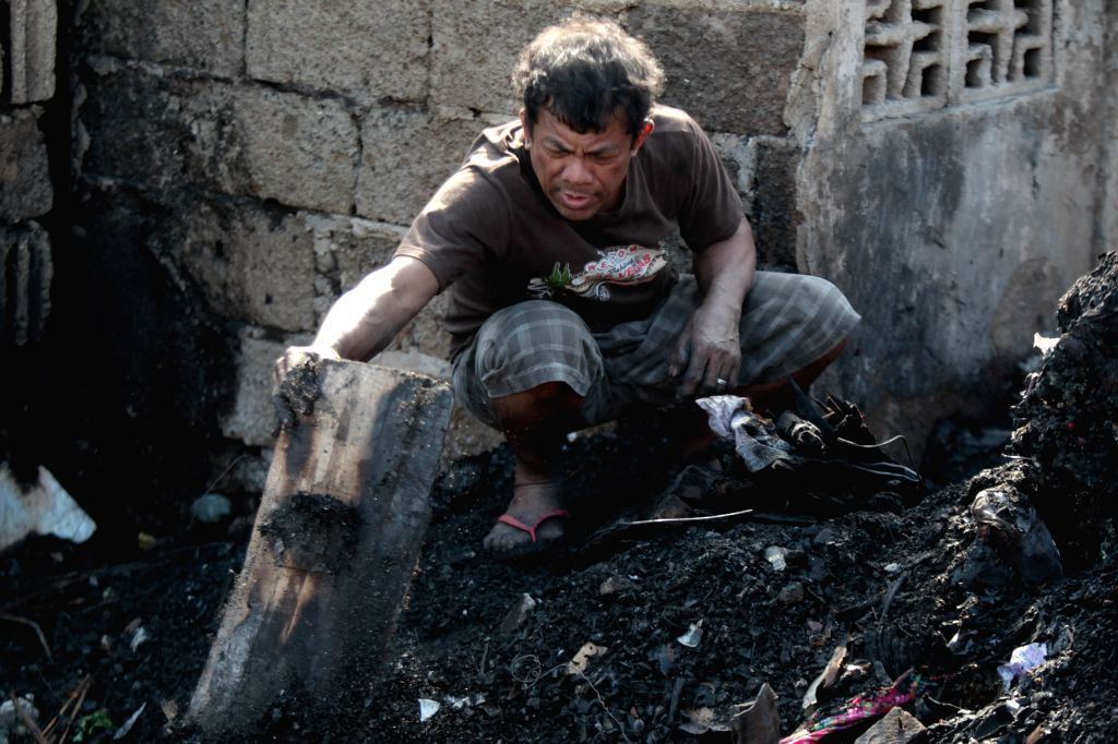 A resident looks for reuseable materials after a fire in a slum area in Pasay City, the Philippines, Feb. 2, 2015. More than 200 houses were razed in the fire, ...
