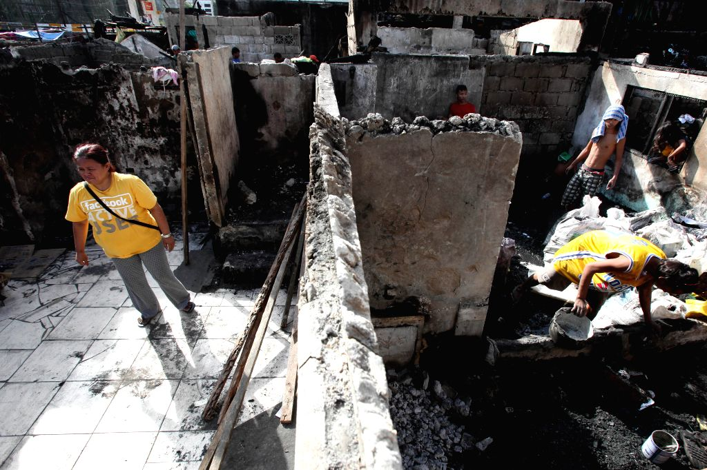 Residents look for reusable materials after a fire in a slum area in Pasay City, the Philippines, Feb. 2, 2015. More than 200 houses were razed in the fire, ...