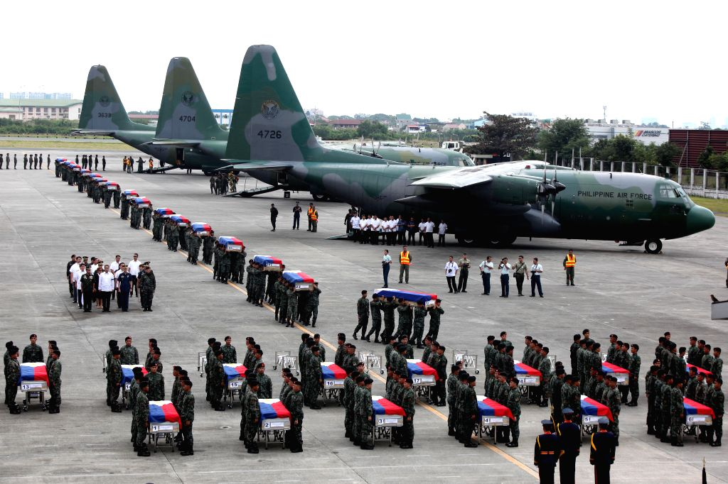 Members of the Philippine National Police Special Action Force (PNP-SAF) carry the caskets of their fallen comrades at the Villamor Air Base in Pasay City, the ..