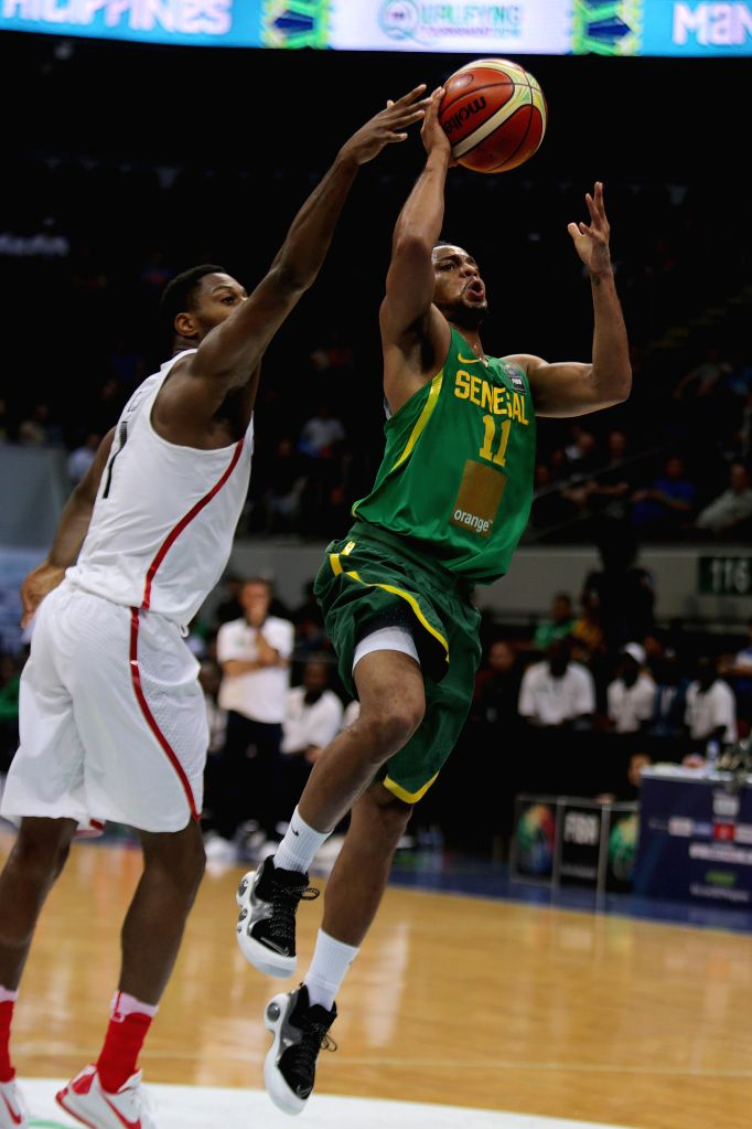 PASAY CITY, July 6, 2016 - Clevin Hannah of Senegal (R) competes against Melvin Ejim of Canada during their FIBA Olympic Qualifying Tournament in Pasay City, the Philippines, July 6, 2016. Canada won ...