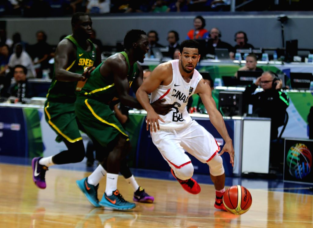 PASAY CITY, July 6, 2016 - Cory Joseph of Canada (R) competes against Thierno Niang (C) of Senegal during their FIBA Olympic Qualifying Tournament in Pasay City, the Philippines, July 6, 2016. Canada ...