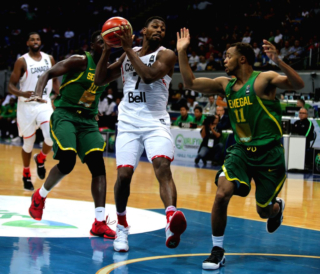 PASAY CITY, July 6, 2016 - Melvin Ejim of Canada (C) competes against Clevin Hanna (R) and Cheikh Mbodj (2nd L) of Senegal during their FIBA Olympic Qualifying Tournament in Pasay City, the ...