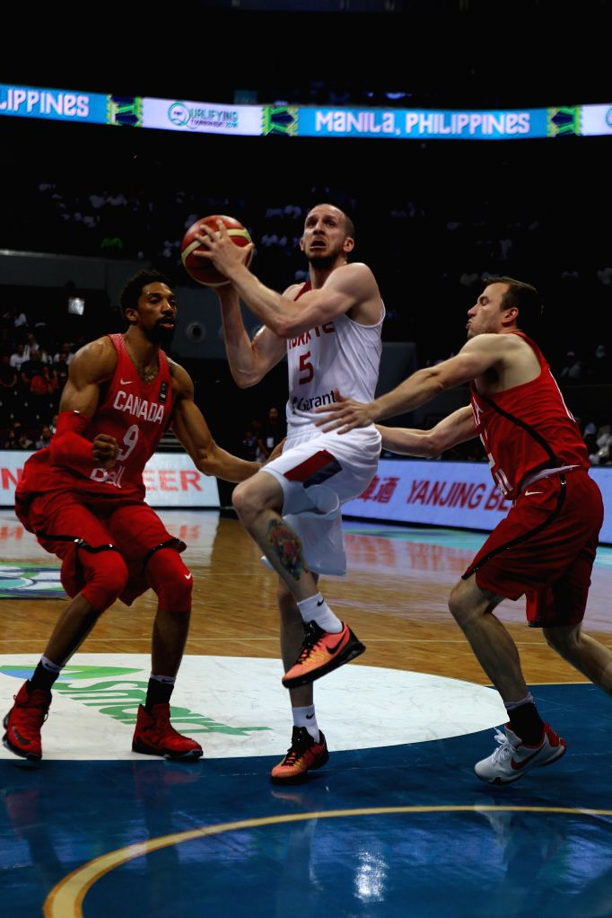 PASAY CITY, July 6, 2016 - Sinan Guler (C) of Turkey competes against Brady Heslip (R) and Khem Birch of Canada during their FIBA Olympic Qualifying Tournament in Pasay City, the Philippines, July 5, ...