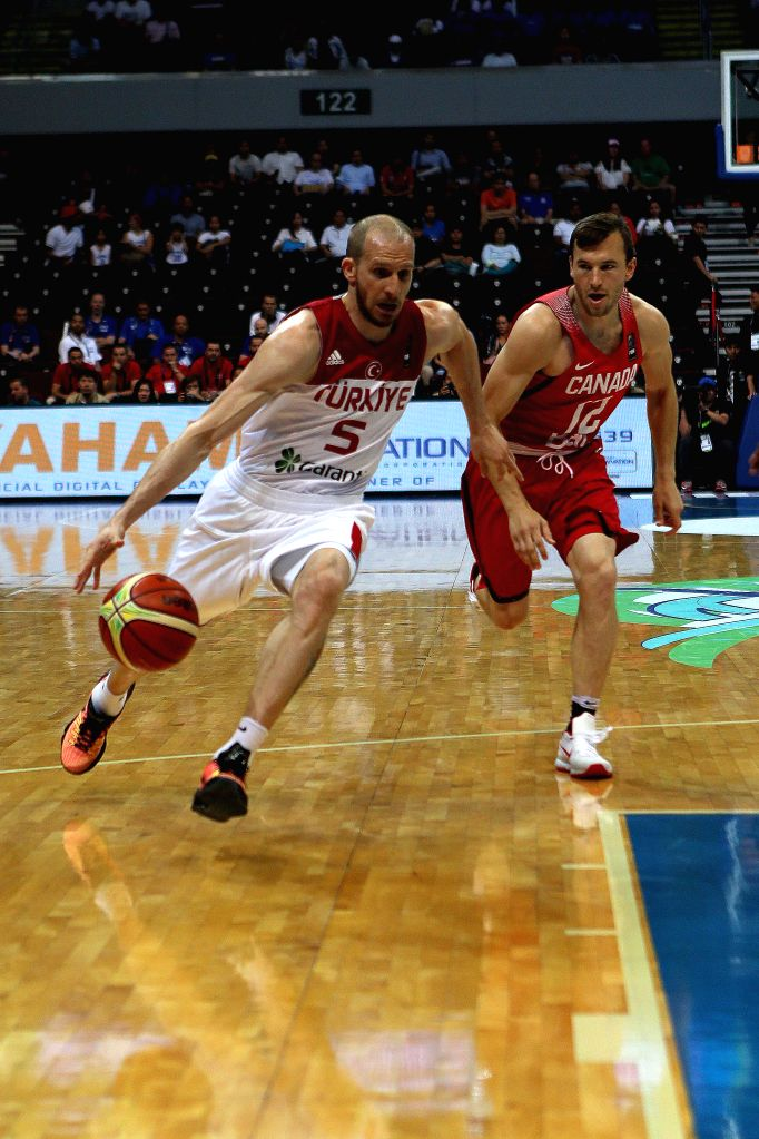 PASAY CITY, July 6, 2016 - Sinan Guler (L) of Turkey competes against Brady Heslip of Canada during their FIBA Olympic Qualifying Tournament in Pasay City, the Philippines, July 5, 2016. Canada won ...