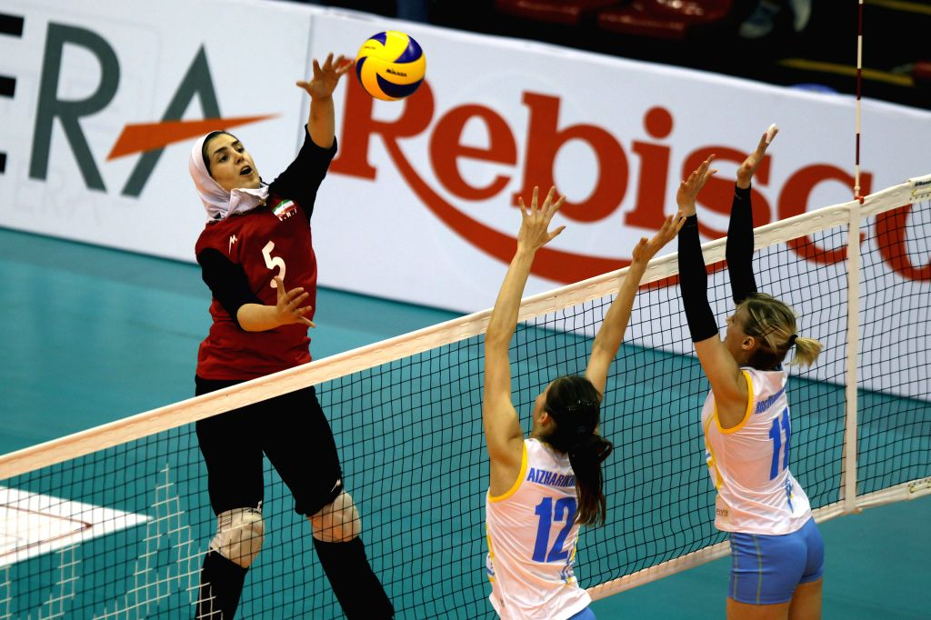 Neda Chamlanian (L) of Iran competes against Anagul Aizharikhova (C) and Anastassiya Rostovchshikova of Kazakhstan during the 1st Asian U-23 Women's Volleyball ...