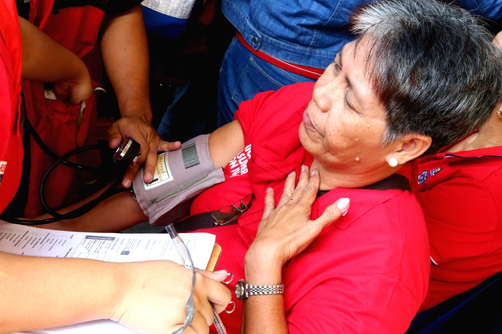 PASIG, July 3, 2019 (Xinhua) -- Medical responders assist a woman who feels sick due to a suspected food poisoning in Pasig City, the Philippines, July 3, 2019. At least 260 people fell ill at the 90th birthday celebration of Imelda Marcos, wife of f