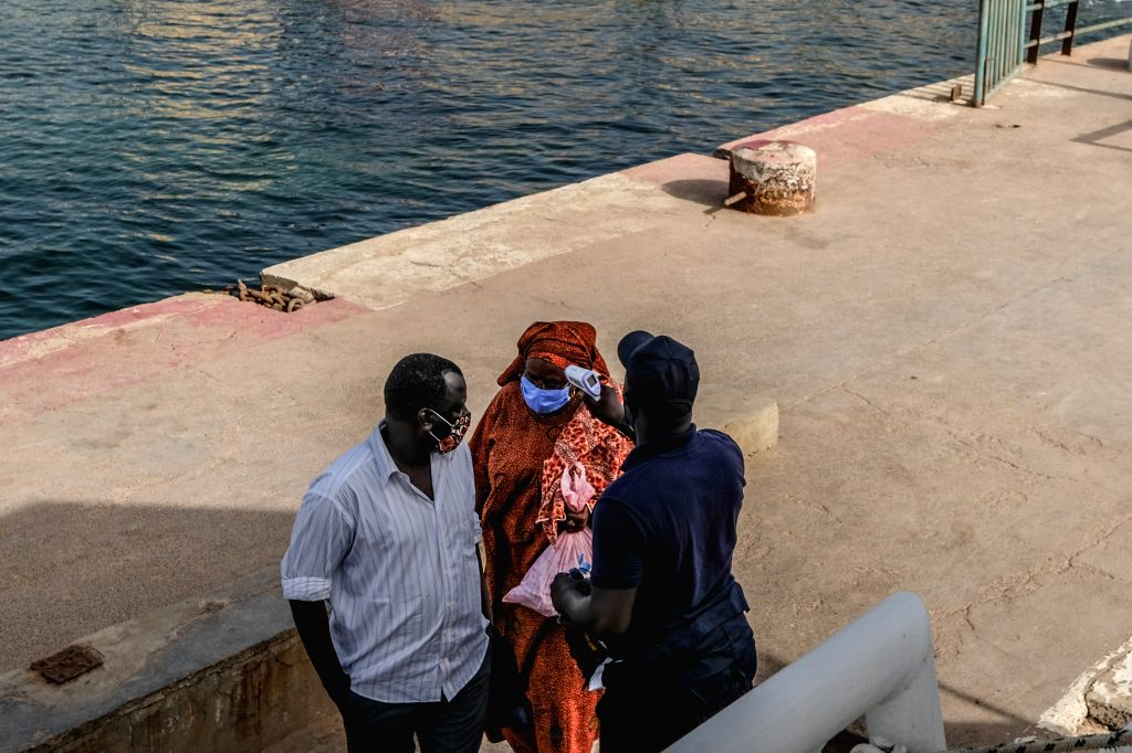 Passengers have their temperature checked before boarding a shuttle boat heading for Dakar on Goree Island, Senegal, on July 1, 2020. Four months after the outbreak of ...