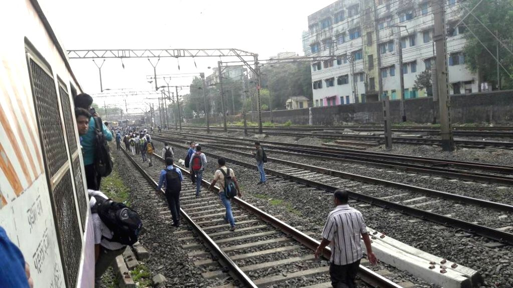 Passengers of Mumbai suburban train walk on the track after the train they were travelling in developed a snag during morning peak hour on May 8, 2017.