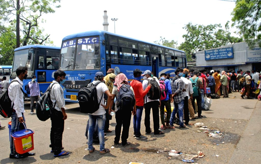 Passengers stand in a queue at a bus stand waiting for the bus during the suspension of local train services across the State in view of the coronavirus disease (Covid-19) situation in ...