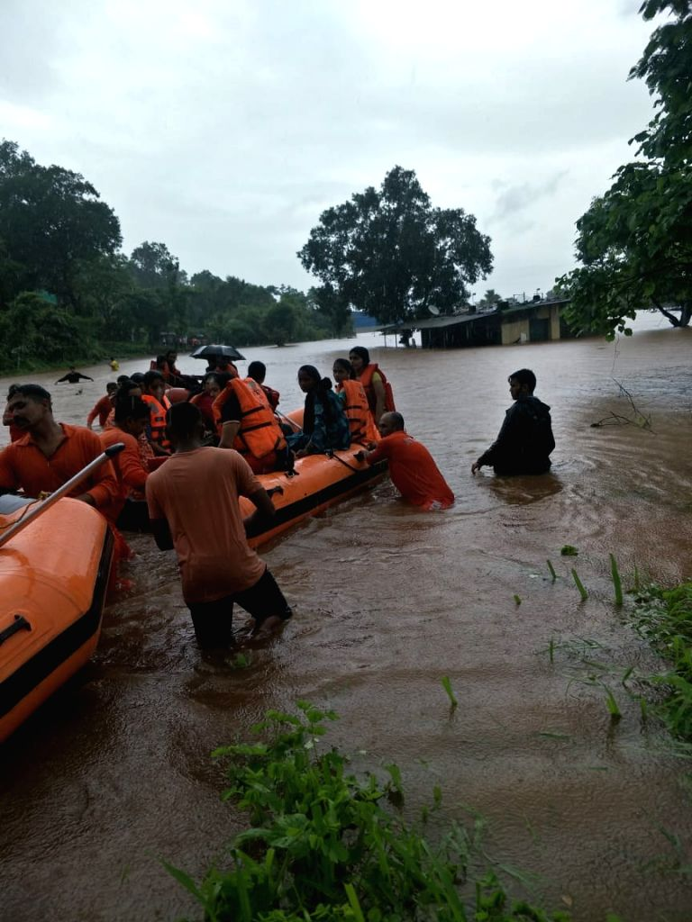 Passengers stranded in the Mahalaxmi Express on the flooded railway tracks at Vangani being rescued, in Maharashtra's Thane on July 27, 2019. The Indian Air Force (IAF), Navy, Army and the ...
