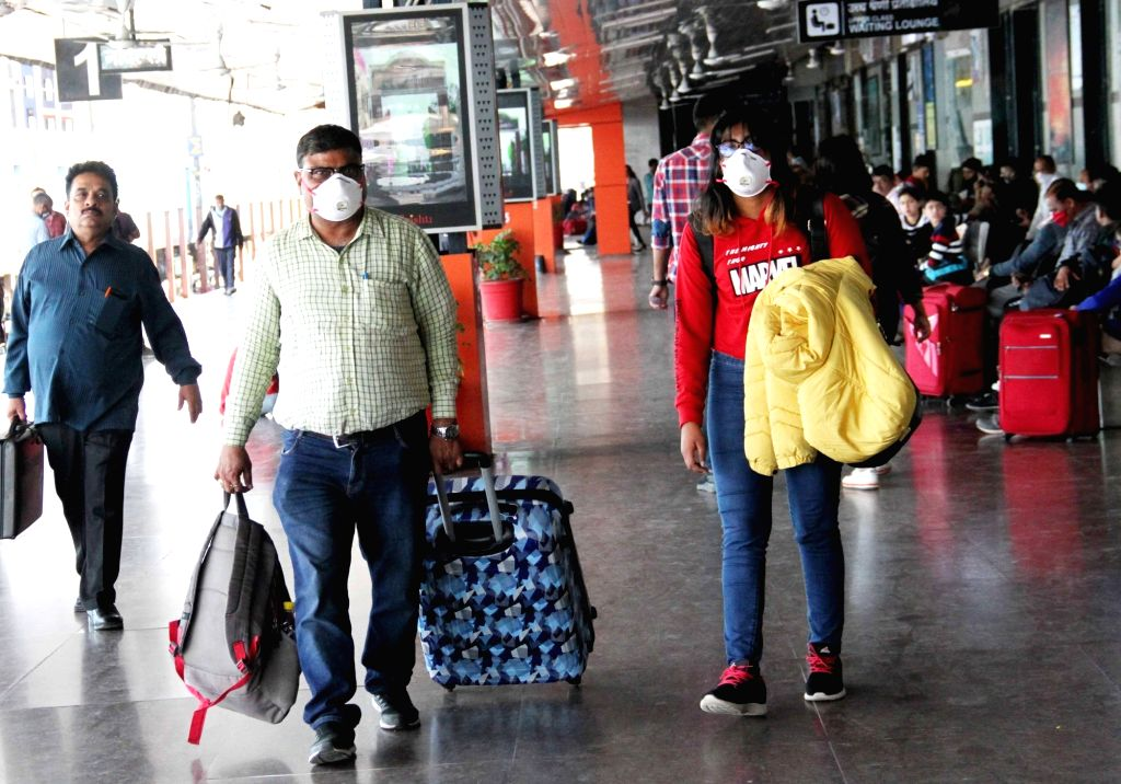 Passengers wear masks as a precautionary measure against COVID-19 amid coronavirus pandemic, at the New Delhi Railway Station on March 18, 2020.