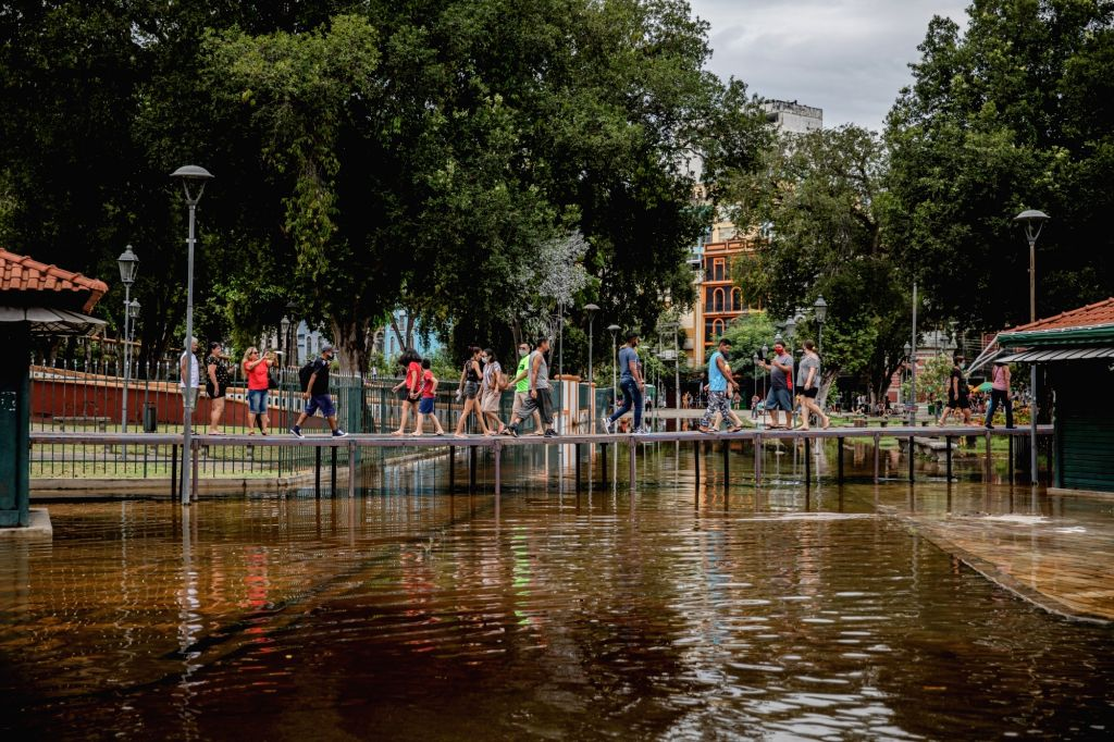 Passers-by walk on temporary bridges over a flooded street after the level of the Rio Negro continued to rise and the floods reached the center of the Amazon metropolis. The level of the river, which ...