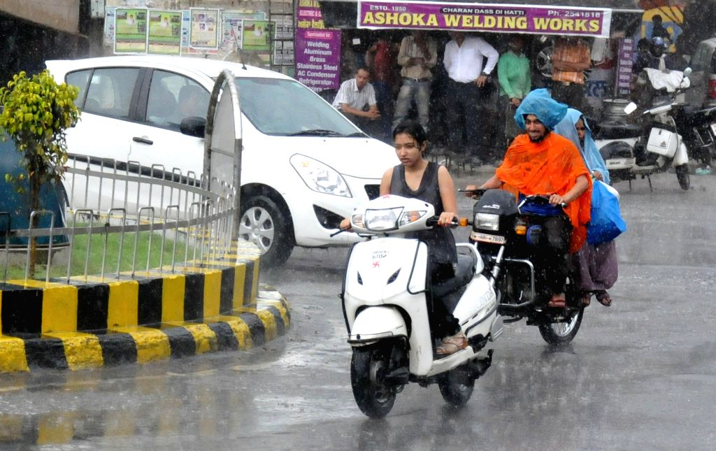 Passers passing through the sudden rainfall during afternoon in Amritsar on June 21, 2014.