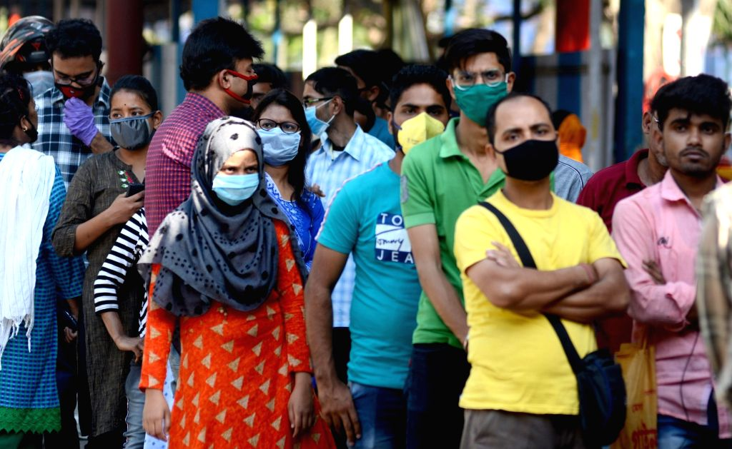 Patients wear masks as a precautionary measure against COVID-19 amid coronavirus pandemic, as they queue up outside the Beleghata ID hospital in Kolkata on March 20, 2020.