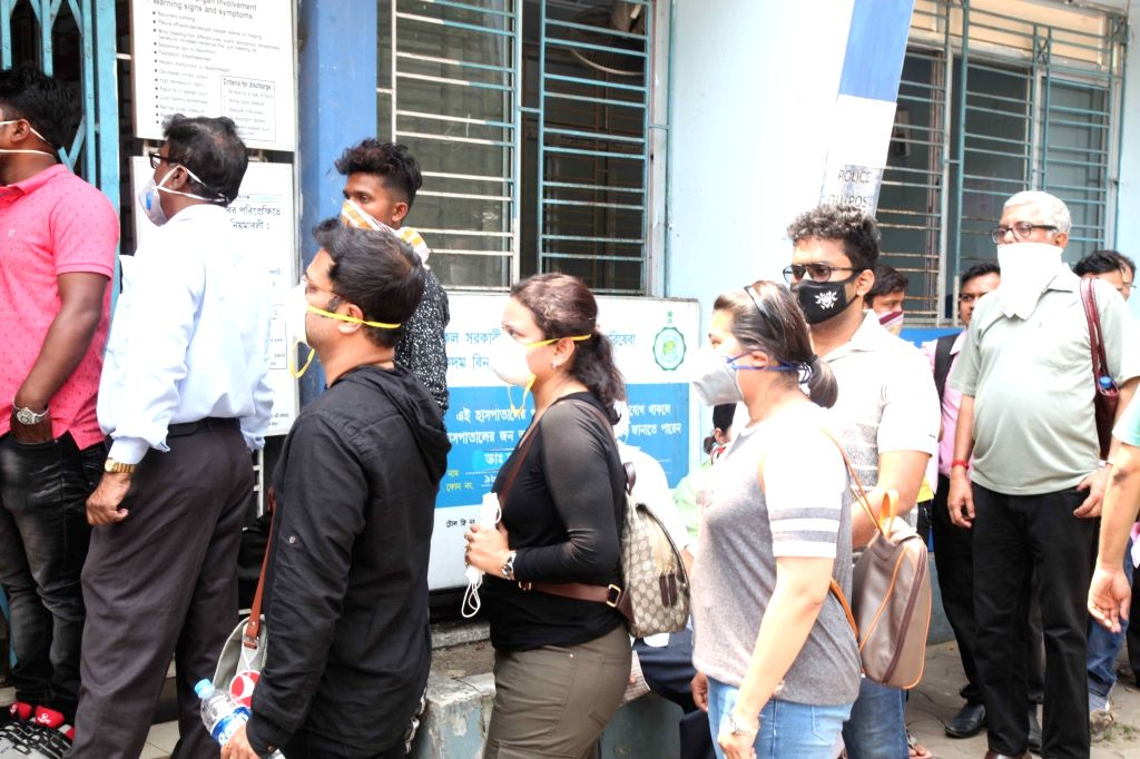 Patients wearing masks wait outside the Beleghata ID hospital amid COVID-19 (coronavirus) pandemic, in Kolkata on March 18, 2020.