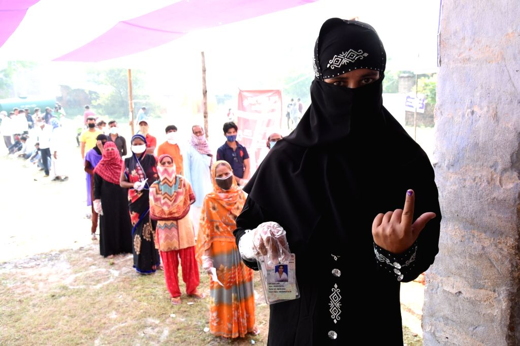 Patna: A Burqa-clad Muslim voter shows her inked finger after casting her vote for the first phase of Bihar Assembly elections, in Patna on Oct 28, 2020. (Photo: IANS)