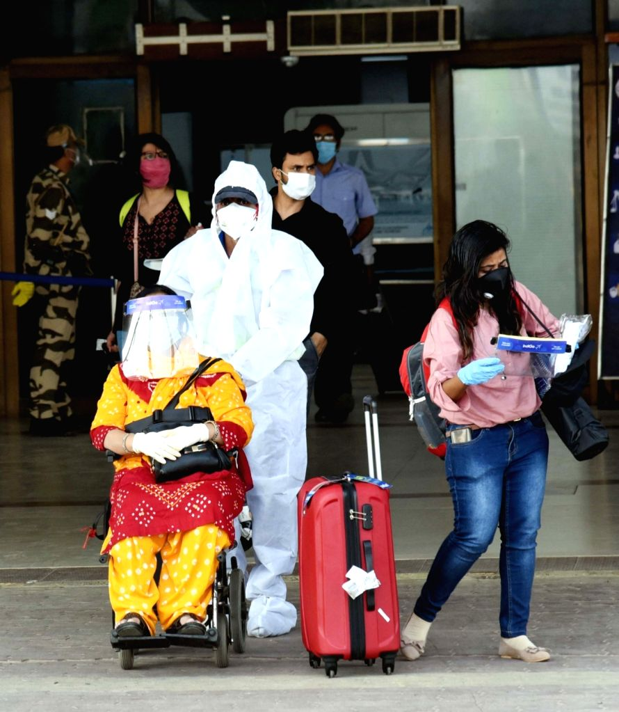 Patna: A staff member wearing Personal Protective Equipment (PPE) suit assists an elderly passenger at the Jai Prakash Narayan International Airport in Patna following the resumption of domestic flights, on the first day of the fifth phase of the nat