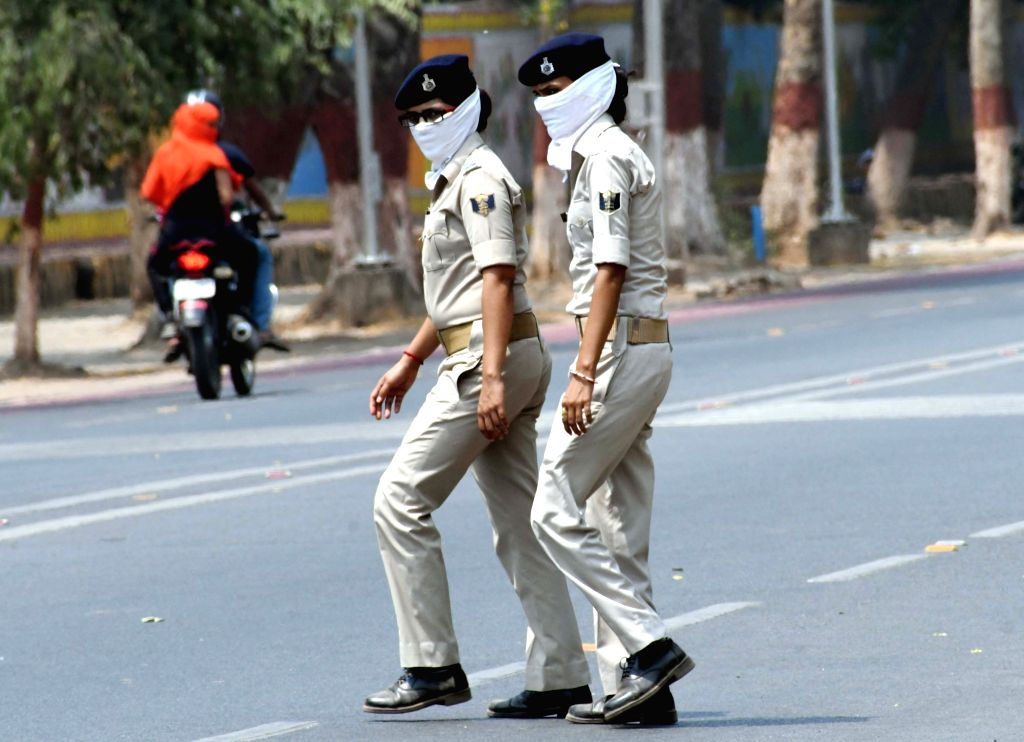 Patna: Bihar Police women personnel cover their faces to shield themselves from the scorching sun on a hot summer day, in Patna on June 15, 2019. (Photo: IANS)