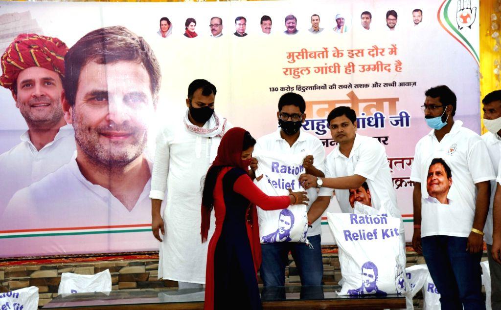 Patna :  Bihar Youth Congress president Rajesh Sinha and Gungan Patel, distribute ration for poor people on the Birth anniversary of Rahul Gandhi in Patna, on Saturday 19 June 2021. - Rajesh Sinha, Gungan Patel and Rahul Gandhi