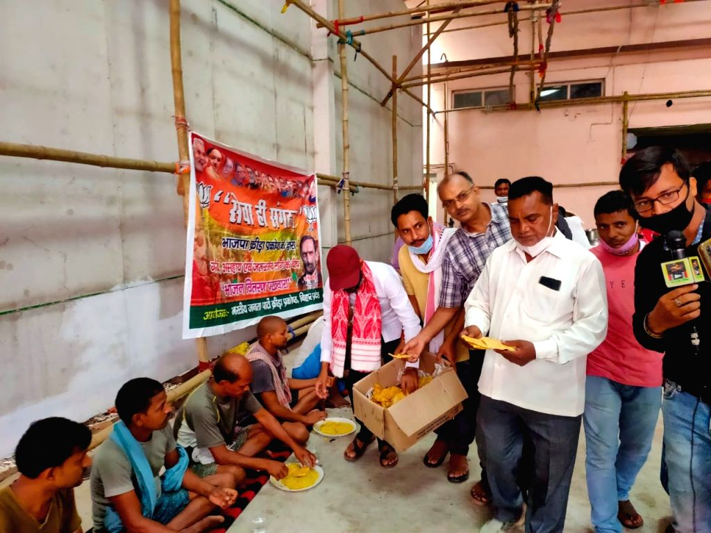 Patna : BJP Sports Cell today distributed masks and food among the needy people of slum settlement near Jain Dharamshala, Mithapur in Patna on Saturday, June 12, 2021.