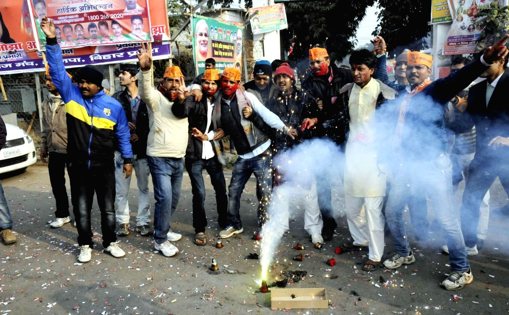 BJP workers celebrate party's performance in Jharkhand and Jammu and Kashmir assembly polls in Patna on Dec 23, 2014.