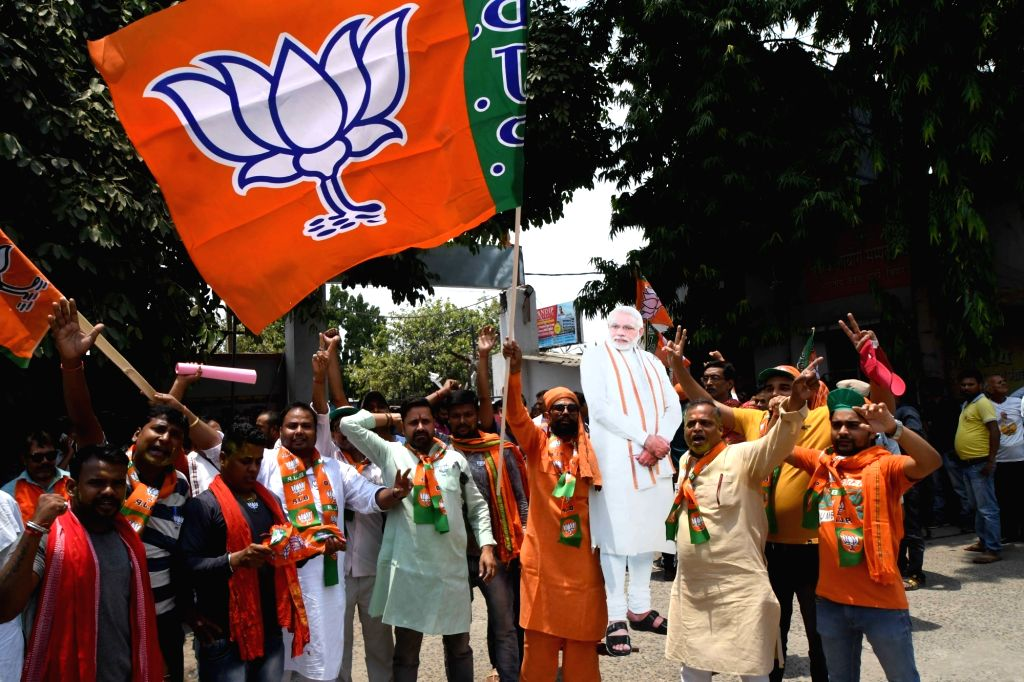 Patna: BJP workers wearing Prime Minister Narendra Modi's masks celebrate after the party led by Prime Minister Narendra Modi was set to retain power for another five years after making a sweep of the 2019 Lok Sabha battle and mauling the opposition; - Narendra Modi