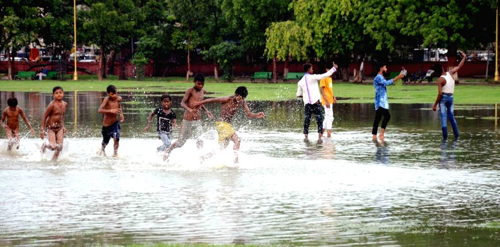 Patna: Children enjoy playing football in a waterlogged football pitch in Patna, on July 8, 2019. (Photo: IANS)